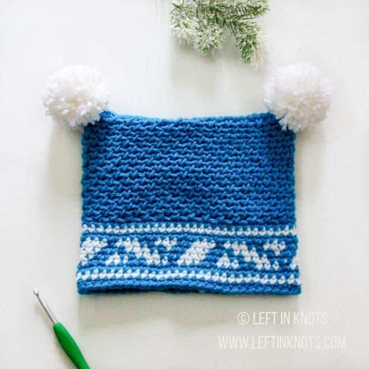 A blue hat for toddlers with two pom poms