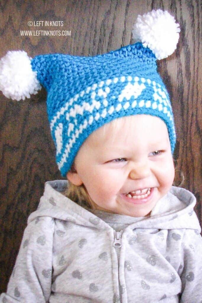 A little girl wearing a crochet double pom hat