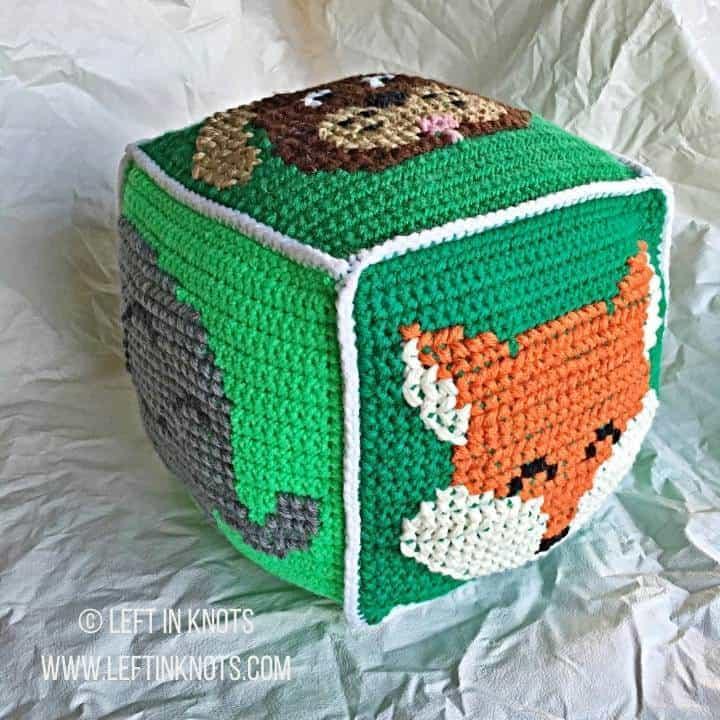 Green crochet block with animals on it