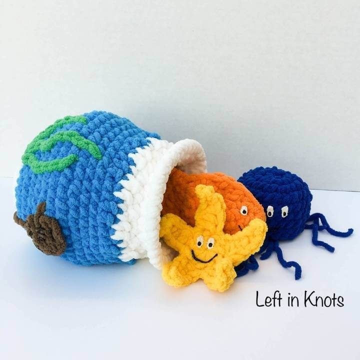 A crochet fish bowl toy with a goldfish, jellyfish and starfish