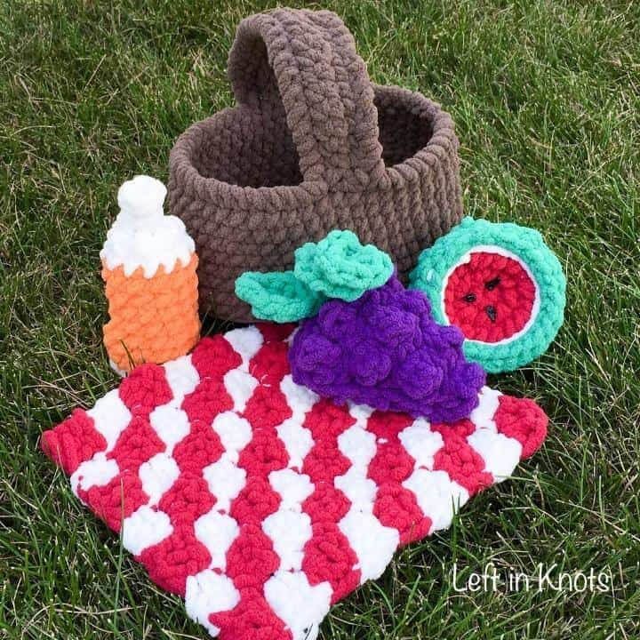 A crochet picnic basket toy in the grass