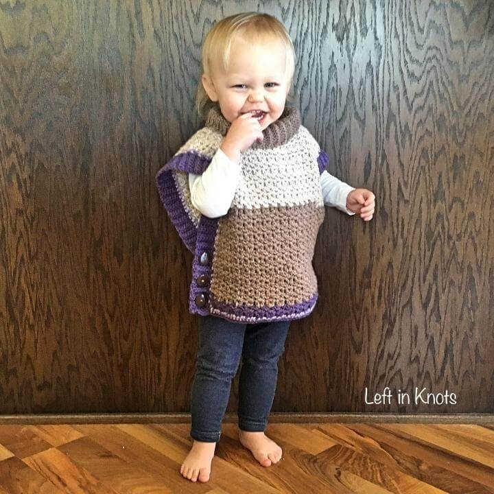 A toddler girl wearing a crochet poncho sweater