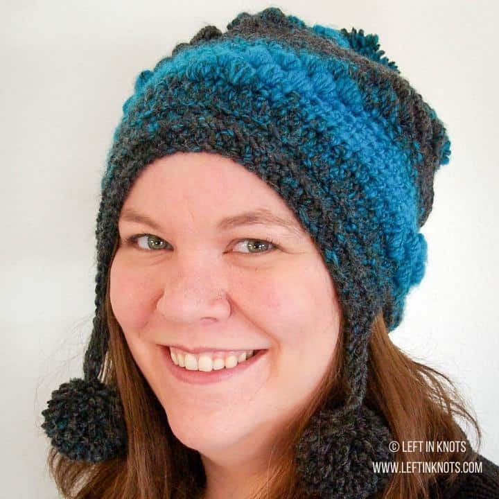 A woman wearing a crochet slouch hat with pom poms
