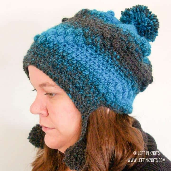 Side view of a woman wearing a crochet hat with pom poms