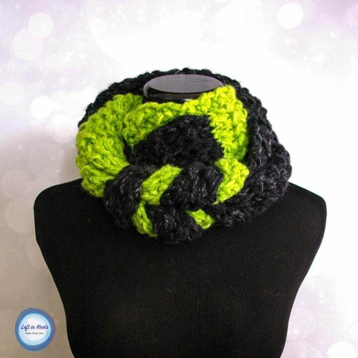 A green and black knotted crochet infinity scarf