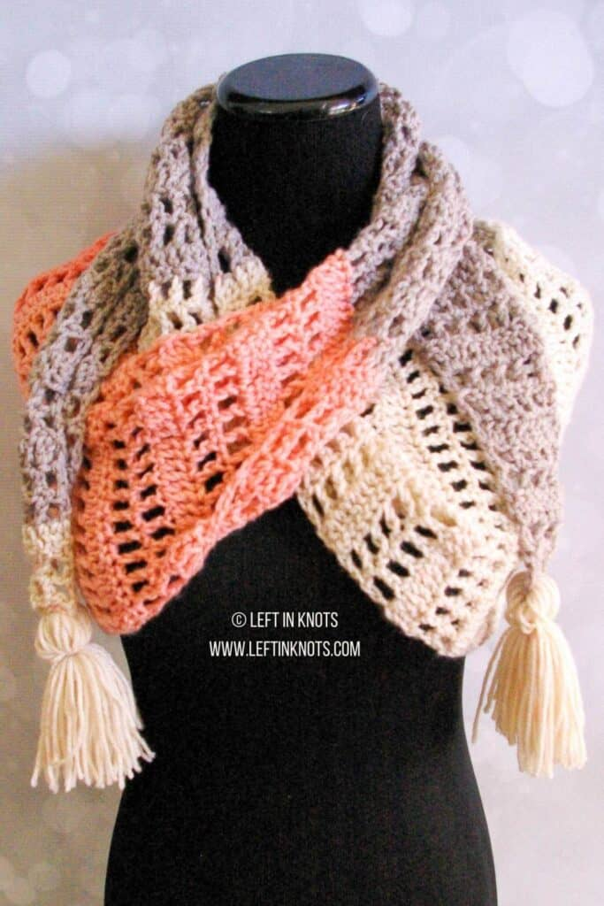 A coral and gray crochet scarf with tassels