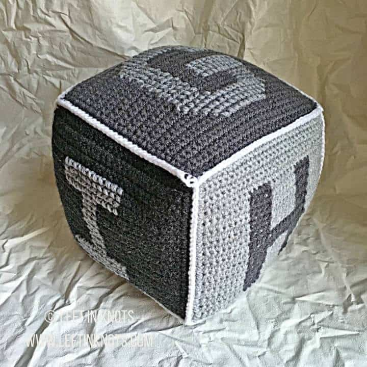 A gray crochet block showing letters of the alphabet G H I