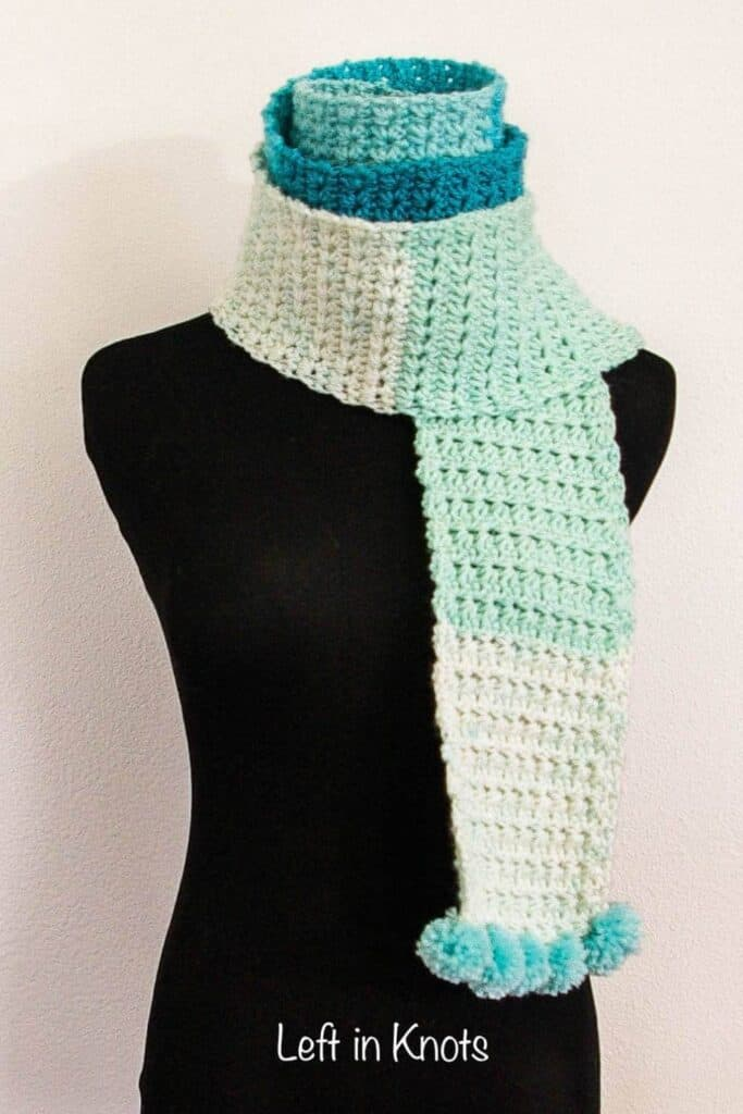 An icy blue and turquoise crochet scarf with pom poms