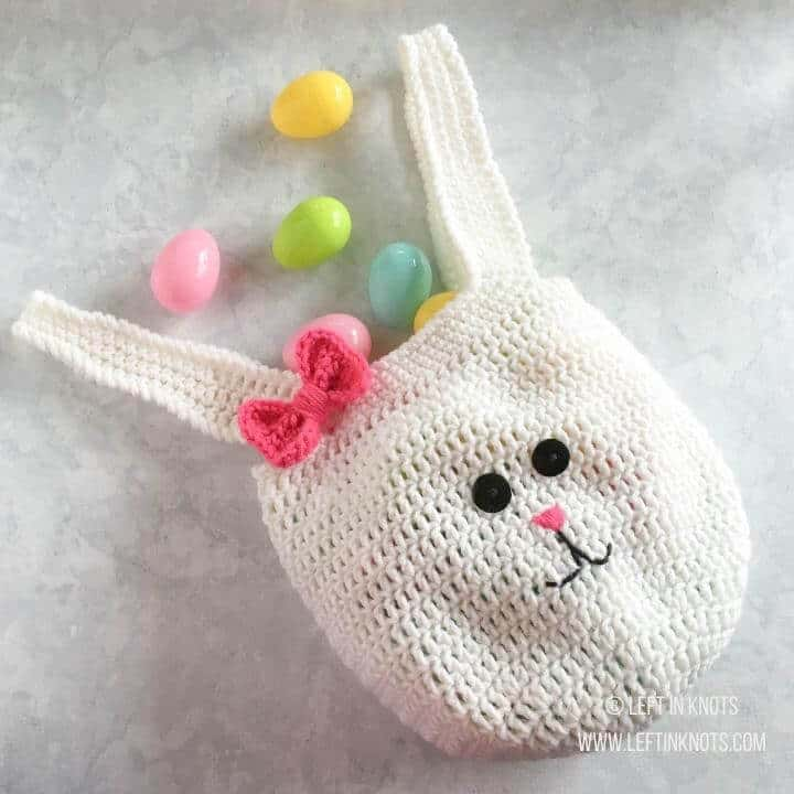 A crochet shaped like a bunny wearing a bow for Easter eggs
