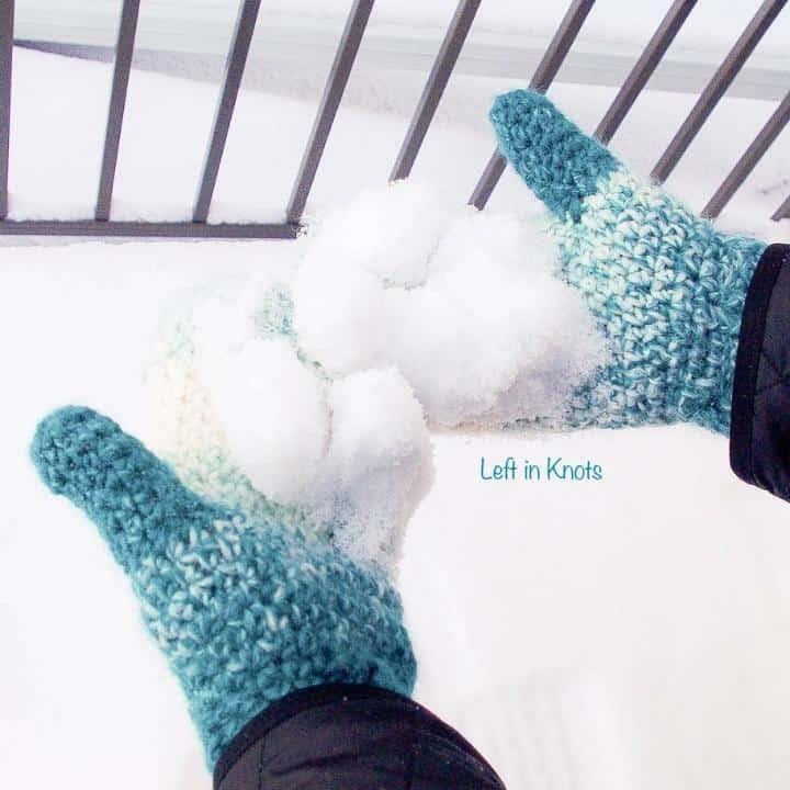 Crochet mittens worn on a woman's hands holding snow