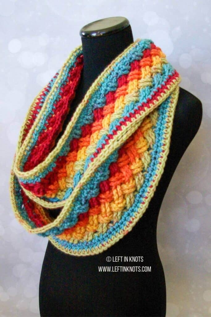 A rainbow crochet infinity scarf made with the Celtic Weave stitch