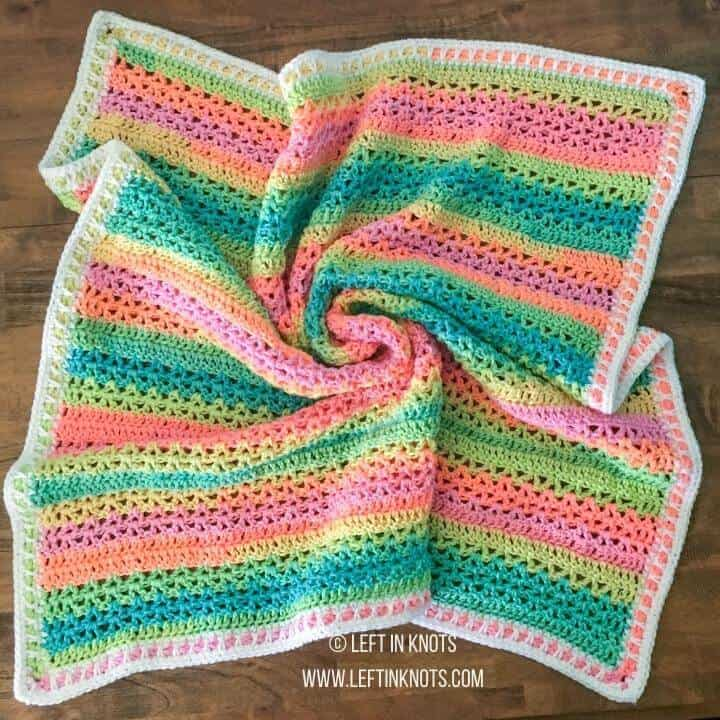A bright neon rainbow crochet baby blanket