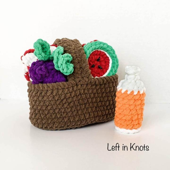 A crochet picnic basket toy filled with food