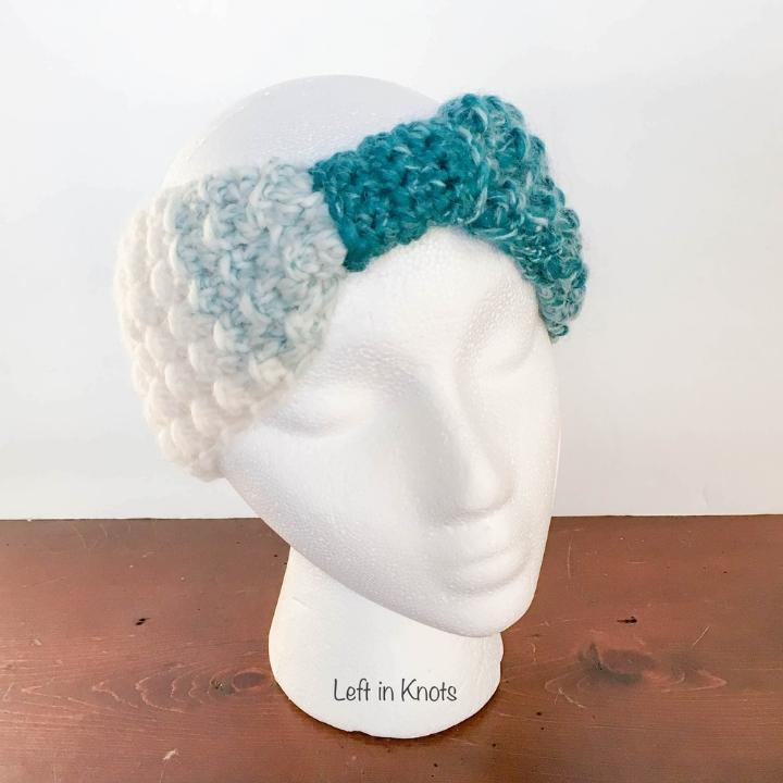 A turquoise and white crochet ear warmer
