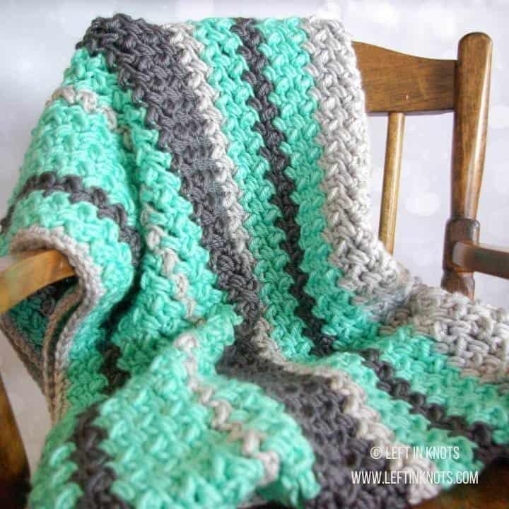 A crochet baby blanket made with chunky yarn and random striping