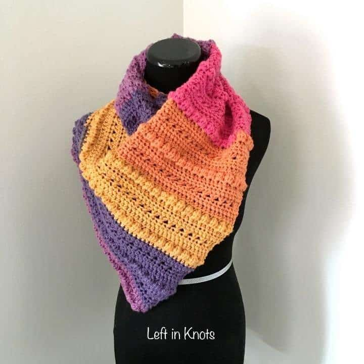An asymmetrical scarf with color blocks of pink orange and purple