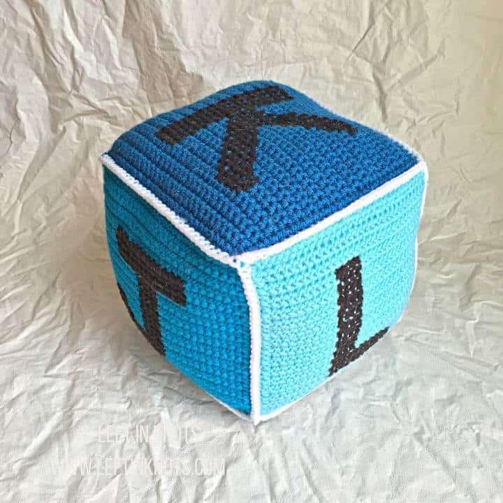 A blue crochet block showing letters of the alphabet J K L