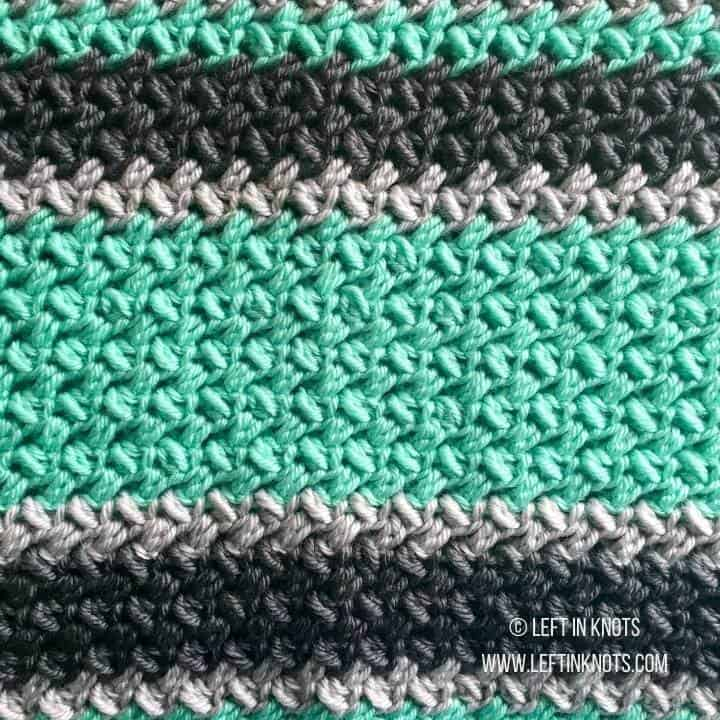 A gender neutral crochet baby blanket made with chunky yarn and random striping