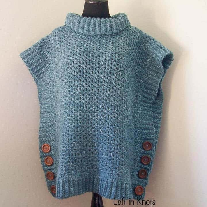 A blue crochet poncho sweater accented with brown buttons