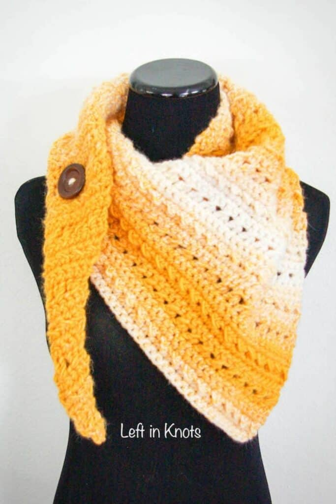 A crochet scarf with a button broach