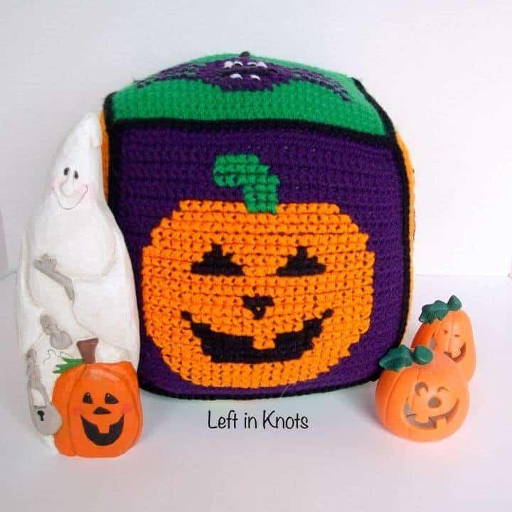 A crochet Halloween pillow block with a Jack-o-lantern
