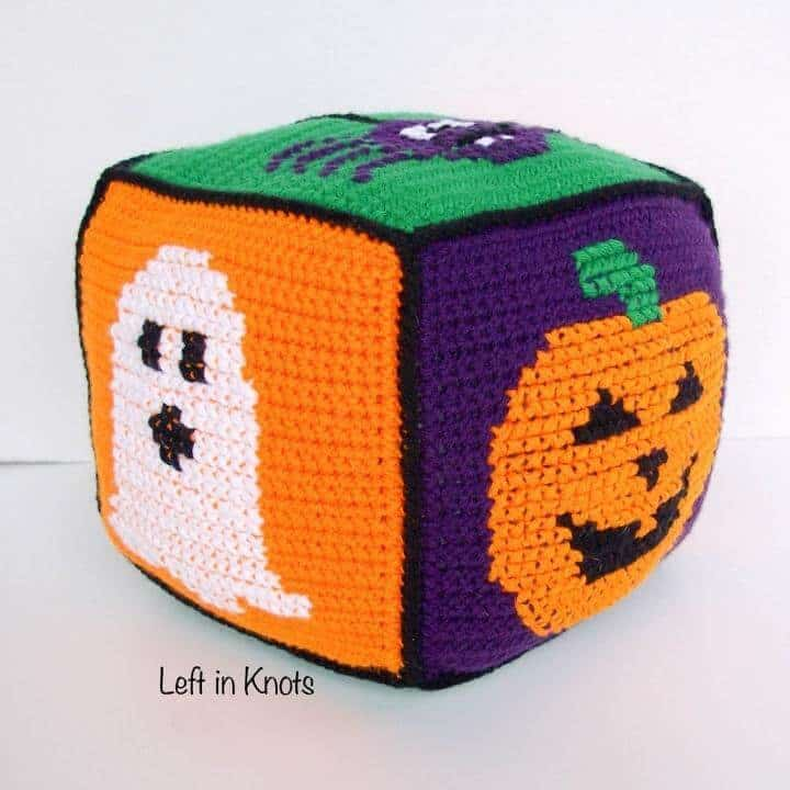 A crochet cube block for Halloween with a ghost, spider and Jack-o-lantern square