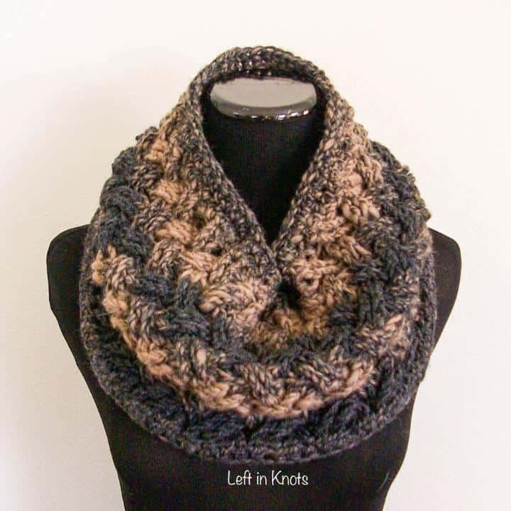 A taupe and charcoal crochet cowl displayed on a mannequin