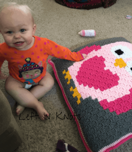 A baby sitting with a crochet owl pillow