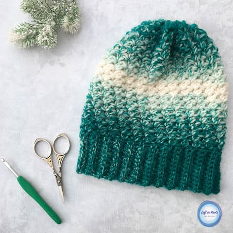 A teal and cream crochet beanie made with the lemon peel stitch