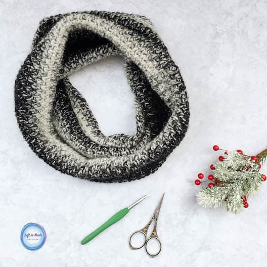 A black and white crochet cowl made with the moss stitch