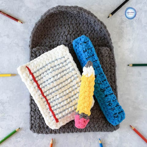 A school supplies baby toy with a crochet pencil, paper and ruler