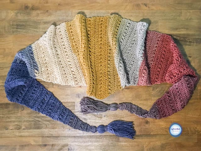 A modern crochet triangle scarf made with textured stitches and tassels