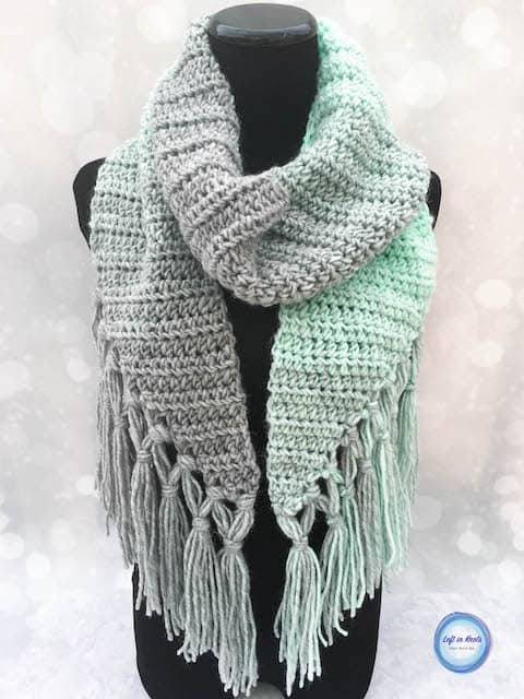 A mint and gray crochet scarf with fringe