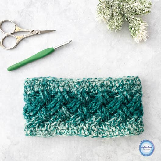 A teal and cream crochet ear warmer made with the Celtic weave stitch