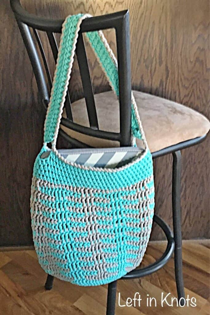 A crochet bag hanging on the back of a chair holding a laptop