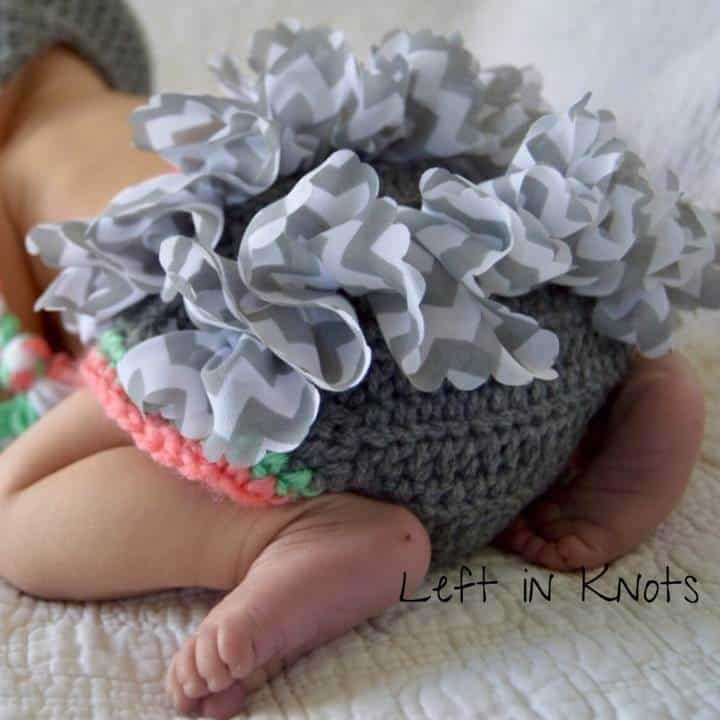 Baby wearing a gray diaper cover with ruffles