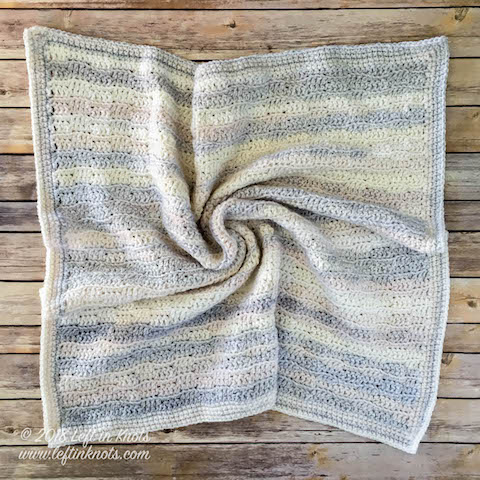 A gender neutral baby blanket made with self striping yarn