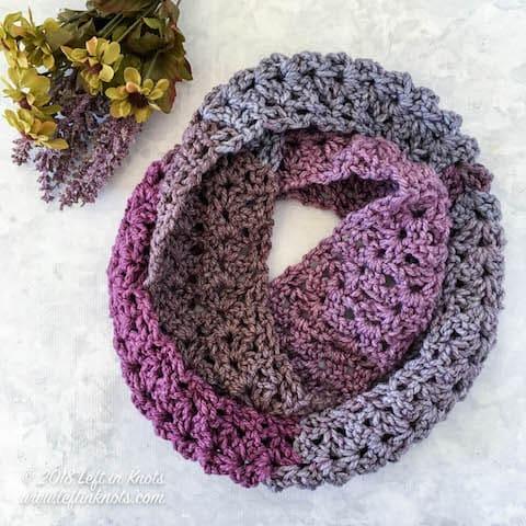 A purple chunky crochet infinity scarf made with the iris stitch