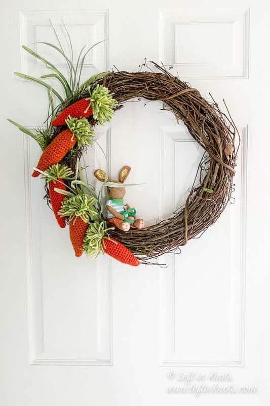 Crochet carrots shown on a door wreath with a bunny