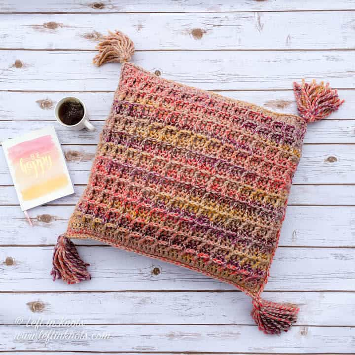 A chunky crochet throw pillow made with the waffle stitch and tassels