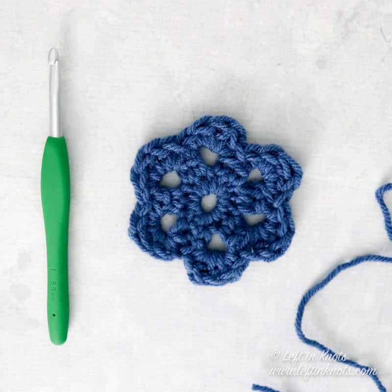 An easy crochet flower shown next to a crochet hook