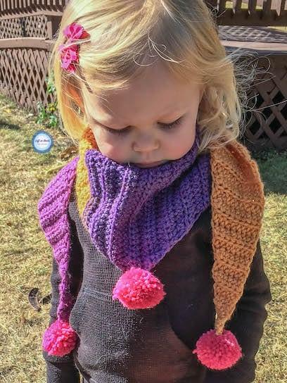 A crochet triangle scarf for kids with pom poms
