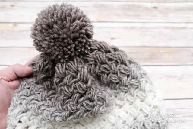 A taupe and cream crochet beanie made with the bean stitch