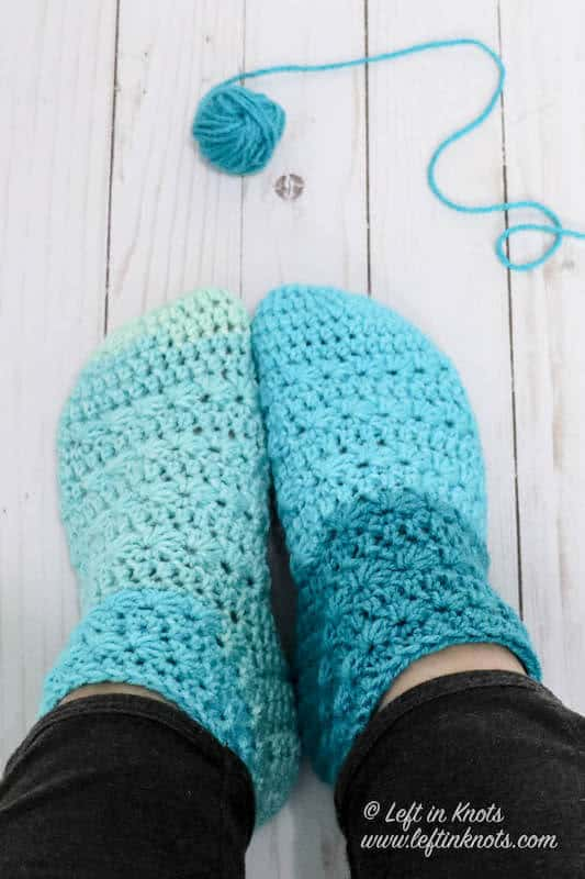 A pair of crochet slipper socks made with Caron Cakes yarn and the star stitch