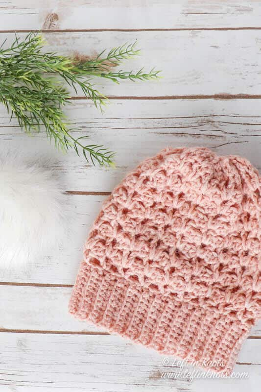 A blush colored crochet beanie made with chainette yarn