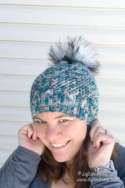 A blue and gray crochet beanie made with hand dyed yarn and a faux fur pom pom