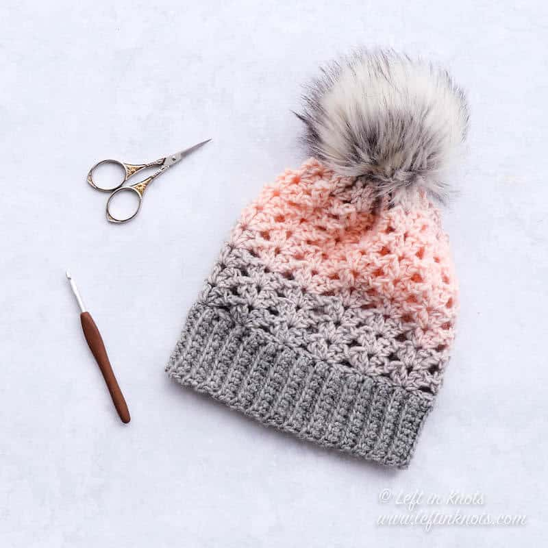 A pink and gray crochet beanie made with the iris stitch