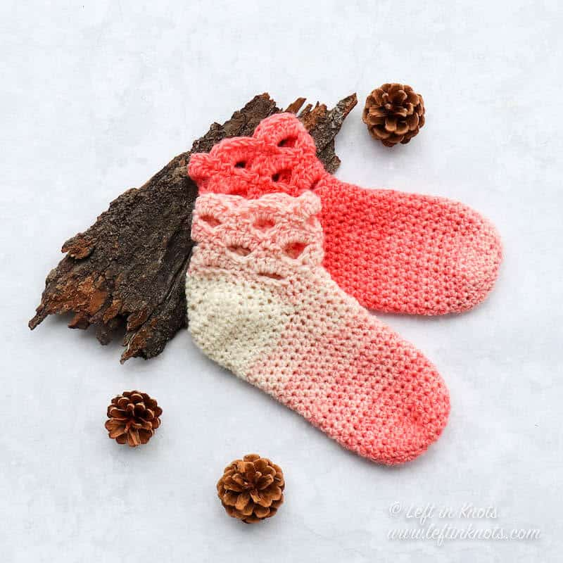 A pair of coral and cream crochet slipper socks made with the arcade stitch