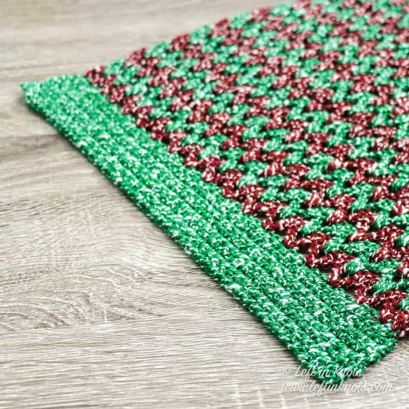 A red and green crochet Christmas table runner