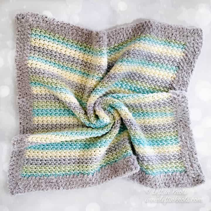 A self striping crochet baby blanket made with the crunch stitch and fuzzy border